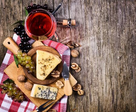 Top view of red wine, grape and cheese on rustic wooden table background with copyspace. French cuisine product from above. Wine and dine still life. Top view.