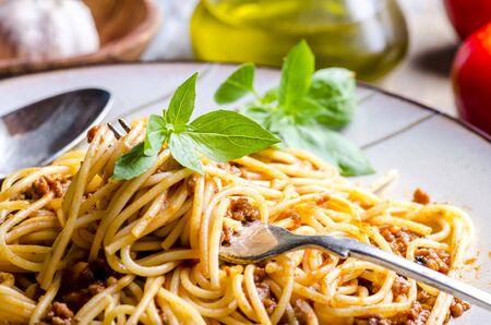 Nahaufnahme der italienischen Spaghetti Bolognese mit Basilikum in der Gabel. Standard-Bild