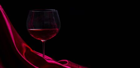 Glass of red wine on red silk against black background. Wine list design background. Luxury restaurant romantic dinner concept.  Stock Photo