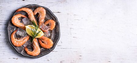 Top view of seafood platter with herbs and spices on white wooden table. Food background with copyspace. Shrimps in vintage plate with lemon from above. Fresh prawns salad dish cooking. Overhead.