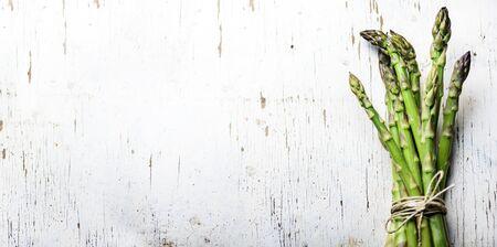 Draufsicht auf frisches grünes Spargelgemüse auf Vintage-Holztisch. Gesunder Lebensmittelhintergrund. Organisches grünes veganes Lebensmittelgeschäft von oben. Design-Layout für die Speisekarte des Restaurants.