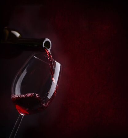 Red wine pouring in wineglass from bottle over dark background. Wine list design menu with copyspace. Alcohol beverage card backdrop.