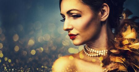 Gorgeous woman with luxury golden makeup on bokeh light glowing background. Sensual lady portrait closeup in retro fashion style. Nightlife party make up and elegant jewellery accessories.