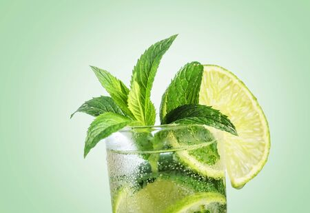 Closeup mojito cocktail with ice isolated over pastel background. Fresh mohito drink with lime and mint. Happy hour and beverage menu design.