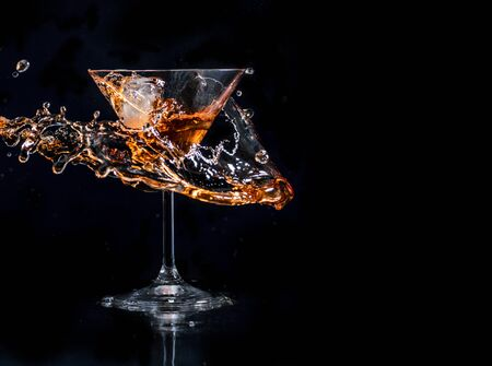 Cocktail splash in martini glass over black background with copyspace. Alcohol drink menu design. Cocktail happy hour and nightlife party concept. Banco de Imagens
