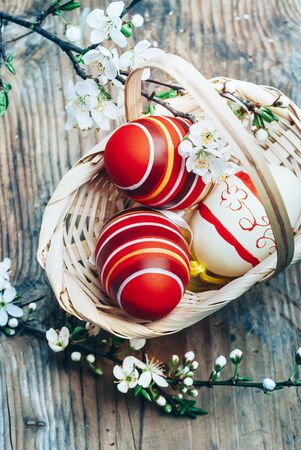 Top view of colorful painted easter eggs in basket and cherry blossom branch decor on vintage wooden table. Traditional seasonal holiday still life from above. Easter celebrate and spring concept.