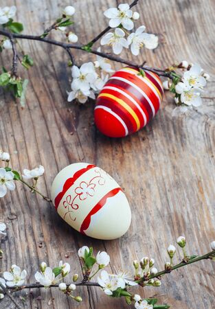 Top view of colorful painted easter eggs and cherry blossom branch decor on vintage wooden table. Traditional seasonal holiday still life from above. Easter celebrate and spring concept.