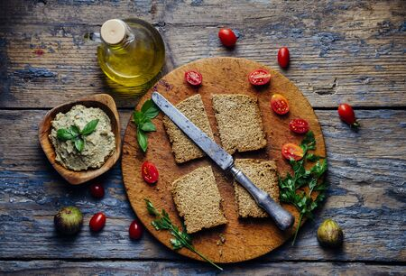 Top view of eggplant tahini dip, bread, cherry tomato and olive oil on vintage wooden table. Mediterranean cuisine still life. Homemade humus with basil from above. Banco de Imagens