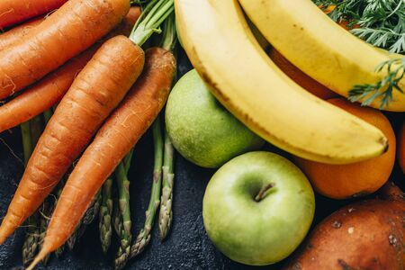Healthy fruits and vegetables delivery from farm market. Organic food ingredients for diet vitamin smoothie recipe. Top view of superfood groceries, citrus, banana, asparagus, carrots, sweet potato and green apples. Colorful summer veggie background.