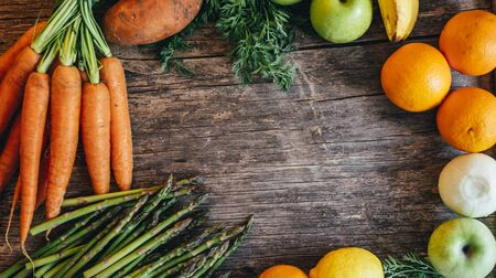 Healthy bio food ingredients frame background from above. Top view of organic superfood border on rustic  wooden table. Colorful fruits and vegetables overhead. Farm market design menu with fresh groceries. Carrot, asparagus, sweet potato, onion, citrus and apples for smoothie recipe.
