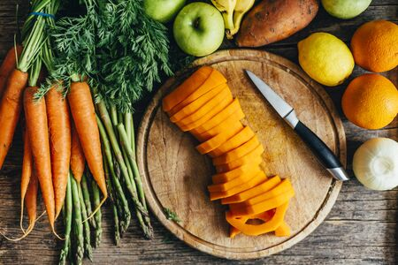 Top view of healthy bio food ingredients for smoothie preparation on wooden table. Organic superfood groceries cooking from above. Colorful fruits and vegetables in kitchen background. Butternut squash, carrots, sweet potato, oranges, apples, carrots and asparagus on cutting board overhead.