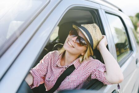 Happy woman travel by car in countryside. Summer vacation in country nature. Young cool people on adventure road trip in mountains. Traveler lifestyle.