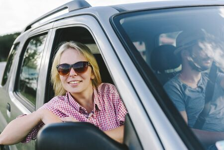 Happy couple travel by car in countryside. Summer vacation in country nature. Young cool people on adventure road trip in mountains. Man and woman on escape romantic weekend tour.