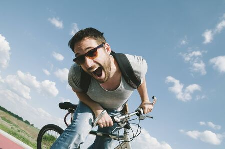 Happy cool hipster guy with bicycle having fun. Summer bike travel adventure in nature. Sexy positive man with excited face cycling on road trip in countryside. Extreme sport and freedom lifestyle.