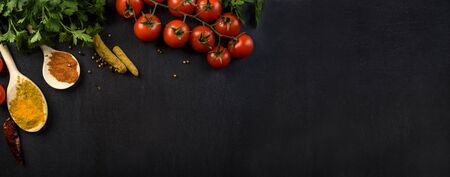Food background with colorful food ingredients border from above. Top view of parsley, cherry tomato, herbs and spices on rustic black table. Culinary recipe banner.