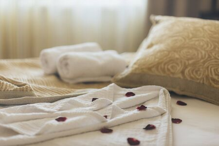 Luxury wellness and spa hotel room arranged for romantic weekend. Honeymoon suite bedroom decorated with rose petals on bed sheets and clean towels. Resort holiday relaxation.