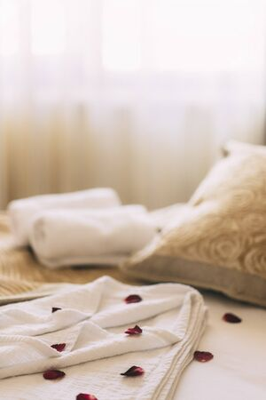 Luxury wellness and spa hotel room arranged for romantic weekend. Honeymoon suite bedroom decorated with rose petals on bed sheets and clean towels. Resort holiday relaxation. Banco de Imagens