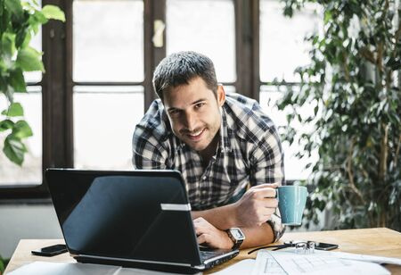 Young man work remote in his cool home office. Modern workspace studio for online business and freelance creative digital project. Internet profession, shopping online, education and e learning concept.