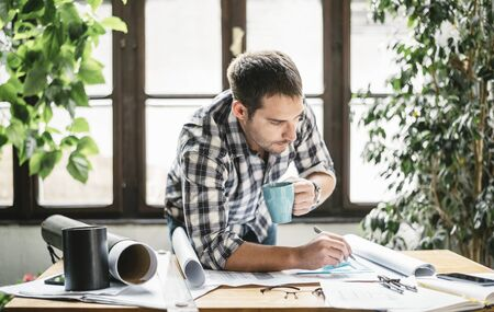 Architect working from home office studio on freelance renovation project. Young freelancer drawing his creative design idea for remote job. Hipster man in cool workspace.