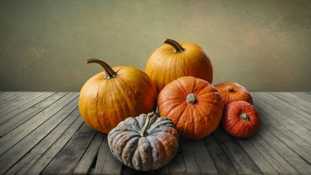 Autumn pumpkins still life on vintage wooden table and rustic background. Thanksgiving family dinner greeting card design. Halloween pumpkin decoration border. Holiday festival concept.