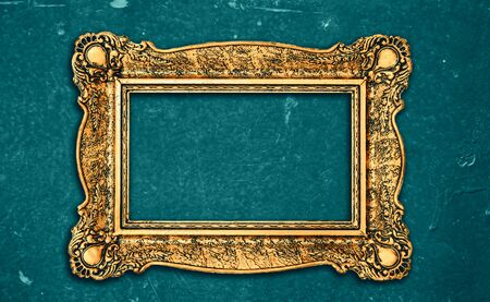 Vintage luxury golden frame with ornate baroque decoration on rustic textured wall background. Retro fancy picture frame for interior design.