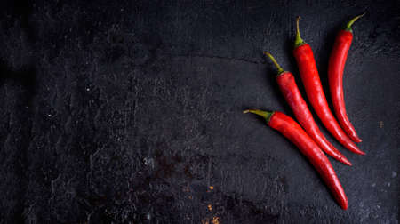 Red hot chili peppers on black rustic textured slate from above. Food background with spicy chilli paprika. Top view.