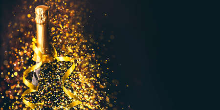 Luxury new year background. Champagne bottle with gold ribbon on dark background with golden bokeh glitter firework. Christmas celebration panoramic design banner.
