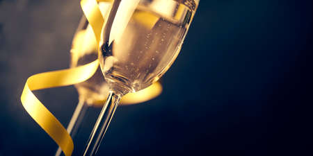 Two champagne glasses with golden ribbon on dark background with copyspace. Luxury restaurant dinner celebration. Classy christmas and new year holiday panoramic design banner.