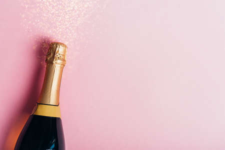 Champagne bottle with gold ribbon on pastel pink background with glitter. New year celebration banner design. Minimal flat lay christmas celebration border. Фото со стока