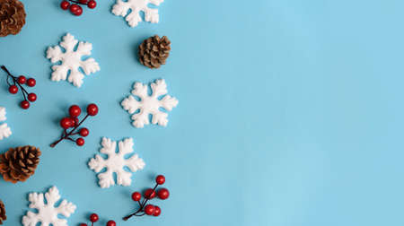 Minimal christmas, new year and winter holiday composition. Flat lay. Creative banner with snow flakes, red berry and pine cone on pastel blue background. Christmas and wintertime concept. Top view.