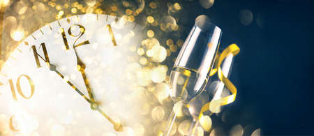 New year eve celebration with champagne flutes and midnight countdown  on golden firework bokeh background. Christmas party with blur confetti glitter, classy drink and vintage clock. Фото со стока