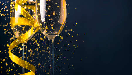 Two champagne glasses with golden ribbon and gold glitter splash bokeh on dark background. Luxury restaurant dinner celebration. Classy christmas and new year holiday panoramic design banner.