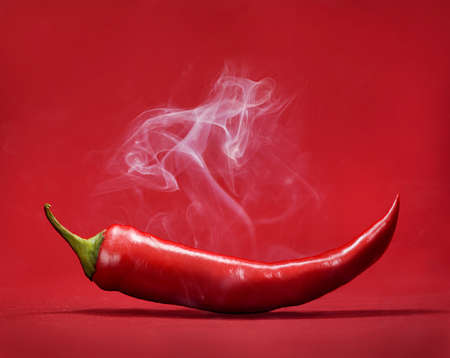 Red hot chili pepper on red background with smoke. Still life with steam mexican paprika spice. Фото со стока