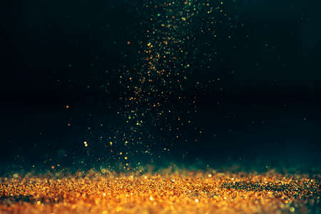 Luxury abstract glitter bokeh background. New year and christmas holiday party design. Golden star dust light sparkling on dark backdrop.