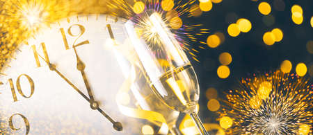 New year eve celebration with champagne flutes and midnight countdown  on golden firework bokeh background. Christmas party with blur confetti glitter, classy drink and vintage clock. Stock Photo