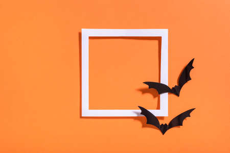 Empty white frame with scary black bats on orange paper. Halloween background layout. Minimal flat lay design.