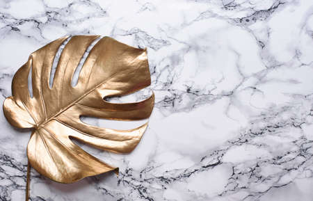 Golden monstera leaf on luxury marble background. Clean minimal flat lay design. Tropical gold foliage for trendy layout. Luxury fashion lifestyle concept.