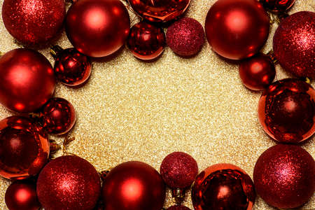 Red Christmas and New year background with christmas bauble frame on golden glitter texture with copyspace. Clean elegant minimal holiday design. Flat lay concept.