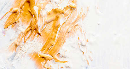 Golden and white oil paint on artist canvas. Fine art gold acrylic color closeup. Abstract creative background texture.