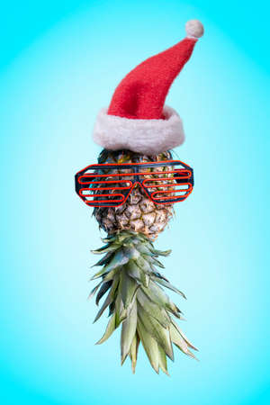 Santa ananas. Funky pop art minimal christmas in summer concept. Funny pineapple with sunglasses and santa claus hat on bright pastel background. Cool holiday creative design.