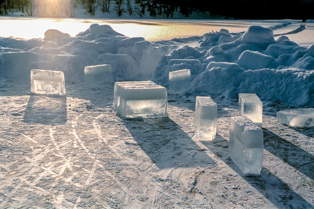 Big frozen ice cubes on an iced lake with snow and sunshine around.