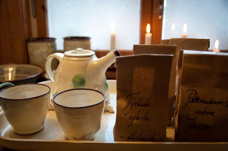 Cozy serving tray with ceramic teacups, teapot, tea and candles in front of window - Brown paper tea bags with the text Turkish organic apple tea and The potters green fruit tea in Norwegian