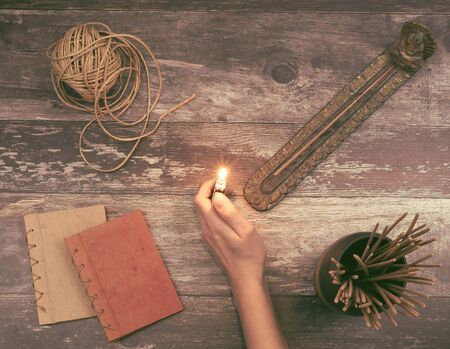 Woman hand lights a incense stick from a Buddha holder on a vintage natural wooden surface with books, hemp twine and many aromatic smelling incense sticks - Concept of spiritual ritual, creativity ideas or imagination