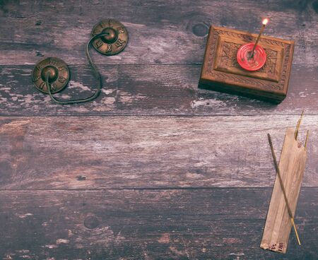 Burning a mystical incense stick in a mindfullness ritual to get a spiritual and peaceful meditation, with copyspace on wood background Banco de Imagens