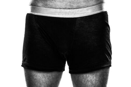 Closeup of a masculine hairy man standing in black boxer shorts isolated on white Banque d'images