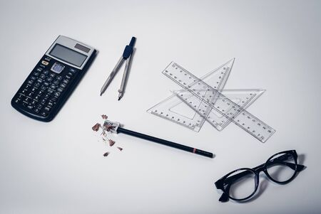Top view of school supplies with calculator, paper compass, rulers, glasses, pencil and sharpener with wooden shavings - Concept of college student, university education, learning or high school Stok Fotoğraf