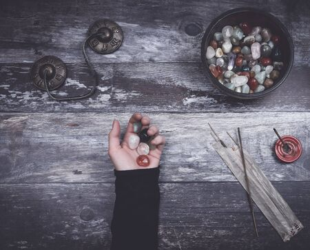 Hand holding small stones in energy healing  meditation on rustic wooden table with burning incense, incense sticks, a bowl of many colorful rounded stones and Tibetan prayer bells with the words Om mani padme hum, commonly translated as The jewel is in the lotus . Banco de Imagens