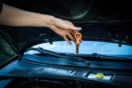 Caucasian white male dirty carpenter hand holding greasy plastic dipstick checking synthetic motor oil level for car engine maintenance.