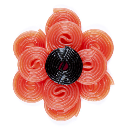 cary: a black licorice wheel on some red licorice wheel on a white