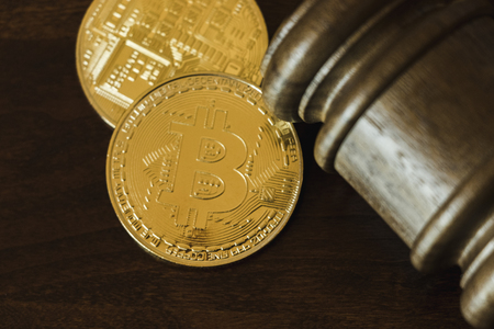 Gold Bitcoin legal concept with wooden gavel on a desk.